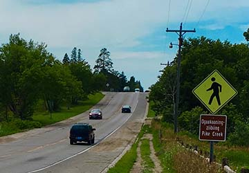 Pedestrian reminder (in Ojibwe) and well-worn footpath on MN-1, Red Lake Reservation, MN.