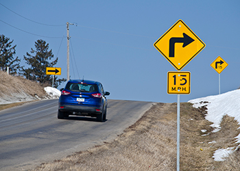 Image of car driving past traffic signs